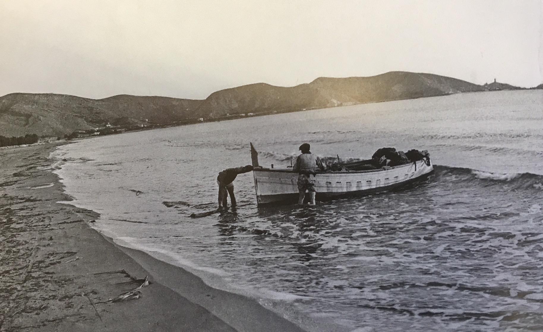 Barca en playa de Cullera y al fondo, el Faro
